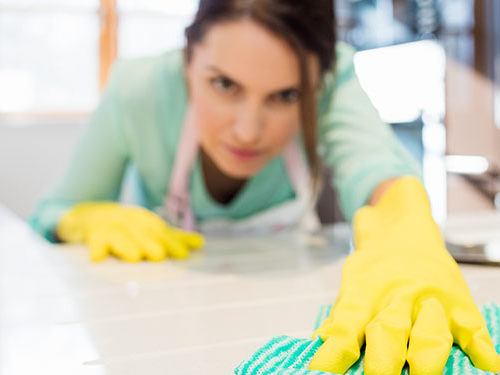 Close-up of woman cleaning kitchen worktop at home